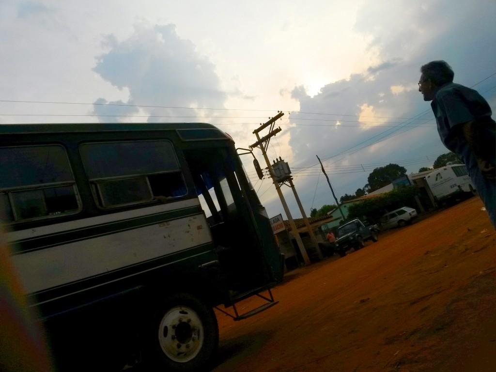La fotografía accidental que para mí, sintetizaría toda esta aventura: Campo y ciudad representados por la tierra y el poste eléctrico, el bus de mi transporte; recorrido incierto, y el personaje mirando a un horizonte con la certeza que después de todo cielo nublado y tormenta, está el día soleado y esperanzador.